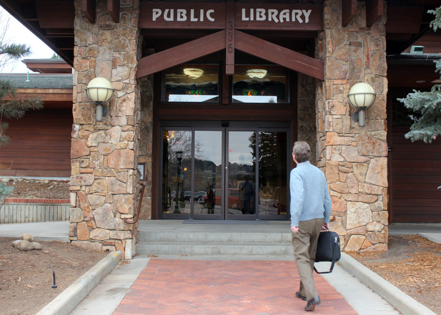 man walking up to entrance of public library