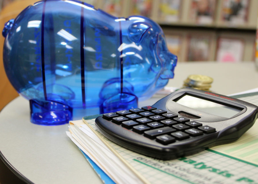 blue piggy bank next to black desk calculator